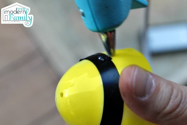 putting hot glue on a yellow plastic easter egg