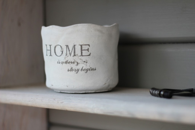 A white ceramic mug sitting on a shelf.
