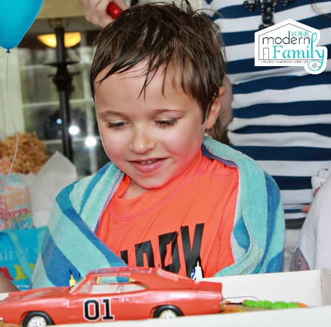 Birthday boy looking at his favorite car on his birthday cake!