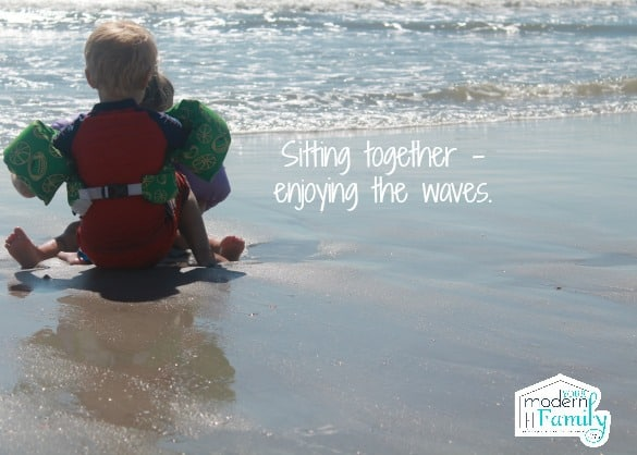 A little girl and a little boy sitting  together at the beach with text beside them.