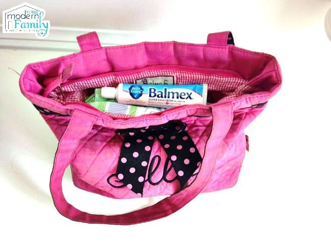 A pink diaper bag with baby supplies inside it.