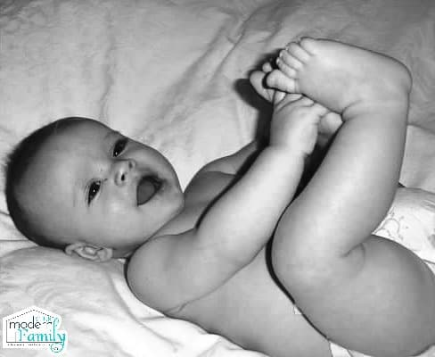 A baby lying on a bed playing with his toes.