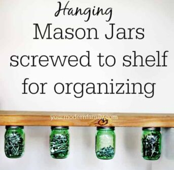Mason jars hanging from a wooden shelf with text above it.