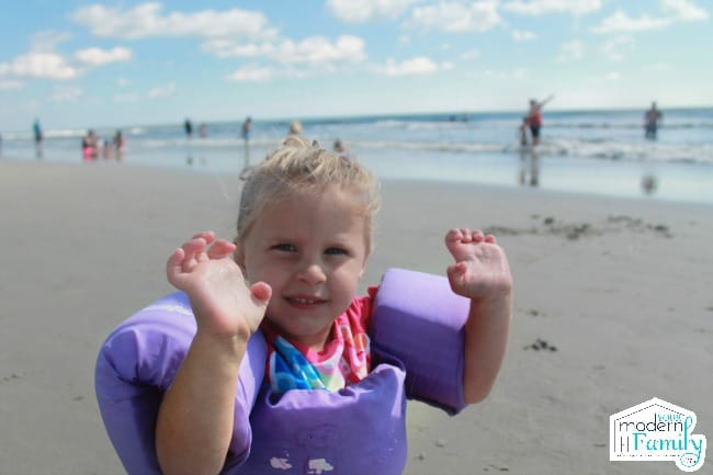 A little girl sitting at a beach wearing a puddle jumper for safety.