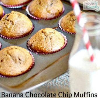 A close up of Banana Chocolate Chip muffins still in a muffin tin with a bottle of white milk beside them.