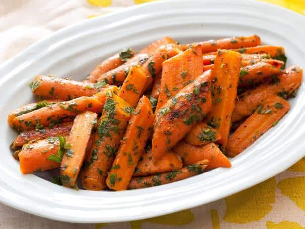A white bowl of roasted carrots with gremolata.