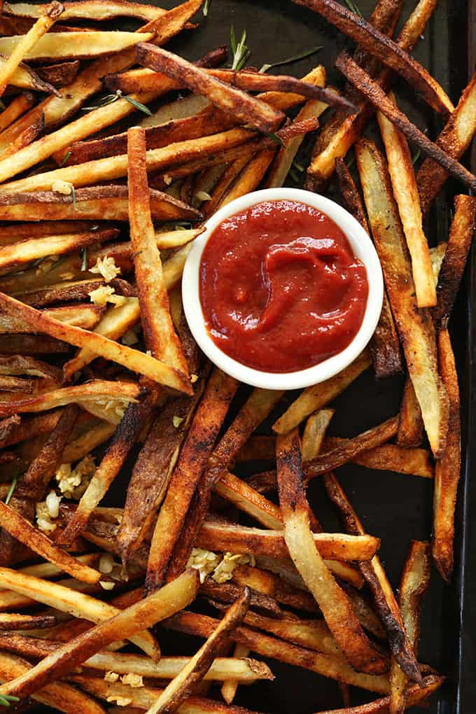A tray of french fries with a cup of ketchup in the middle.