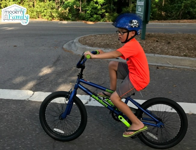 A little boy wearing a helmet and riding a bicycle.