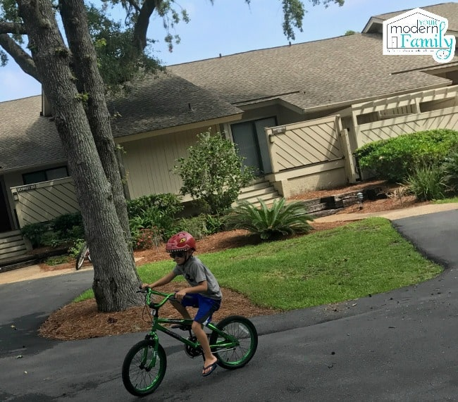 A boy riding a bicycle on the side of a road.