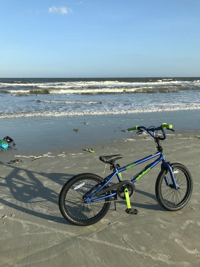 A bicycle parked on a beach.