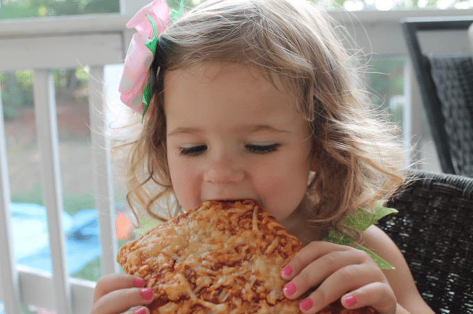 A little girl eating a slice of pizza.