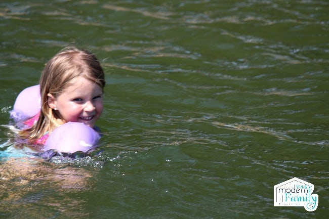 A little girl in the lake water looking at the camera.