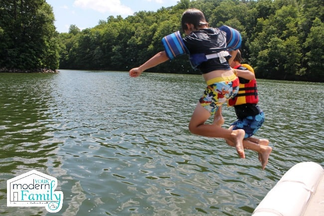 Two kids jumping onto water.