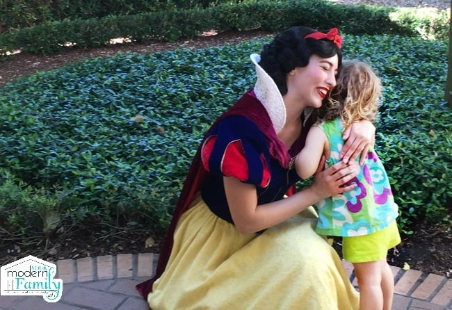 A little girl hugging a Snow White character.