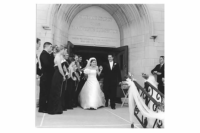 A wedding couple exiting a church with bridal party watching.
