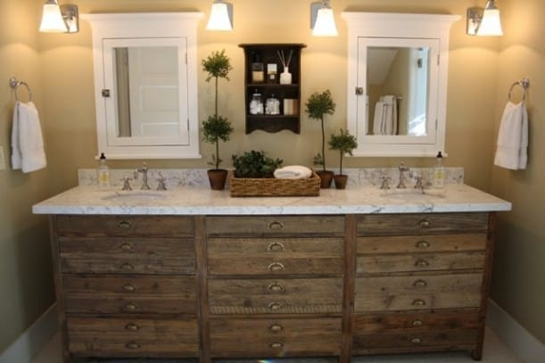 A bathroom cabinet with numerous drawers and double sinks and mirrors.