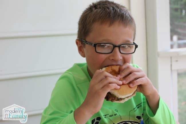 A boy wearing a green shirt eating a hamburger.
