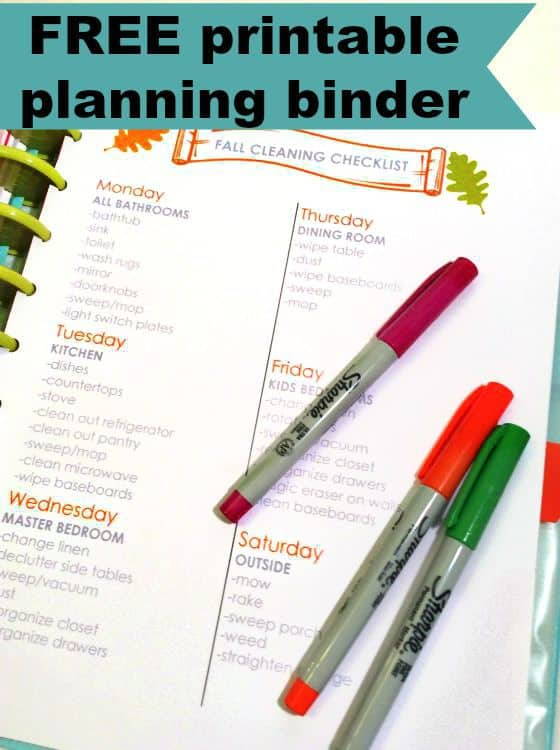 A close up of an open planner with three different colored  markers resting on it.