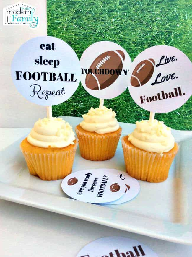 Cupcakes with straws stuck in them holding decorative football toppers.