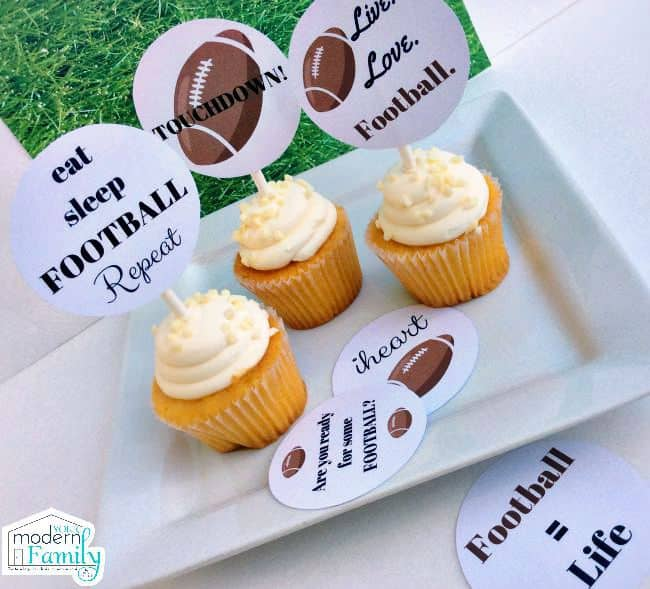 Cupcakes with straws in them holding decorative football toppers.
