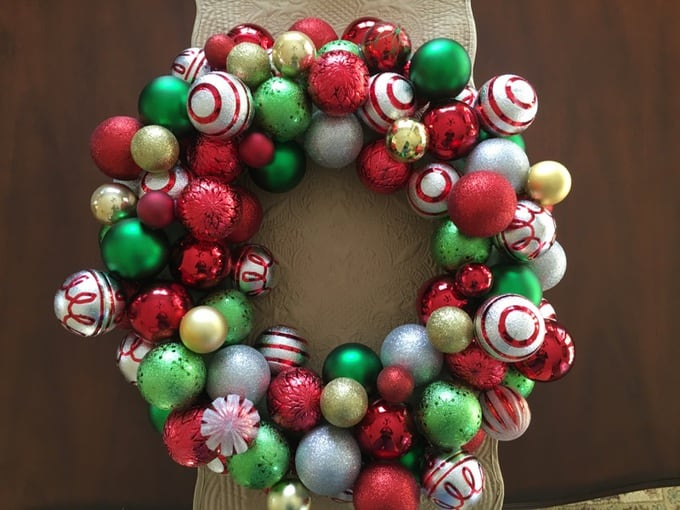 A completed Christmas wreath decorated with Christmas ornaments.