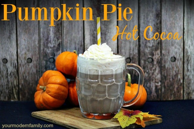 A cup of Pumpkin Pie Hot Chocolate with fall themed items on the table and text above them.