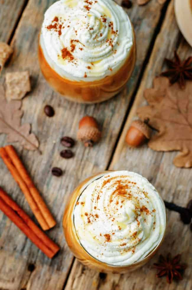 Two cups of Pumpkin Pie Hot Chocolate with fall themed decorations on the table.