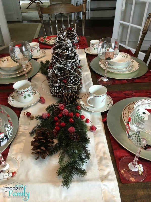 A dining table set with Christmas plates and decorations.