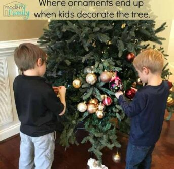 Two boys decorating a Christmas tree with text above them.
