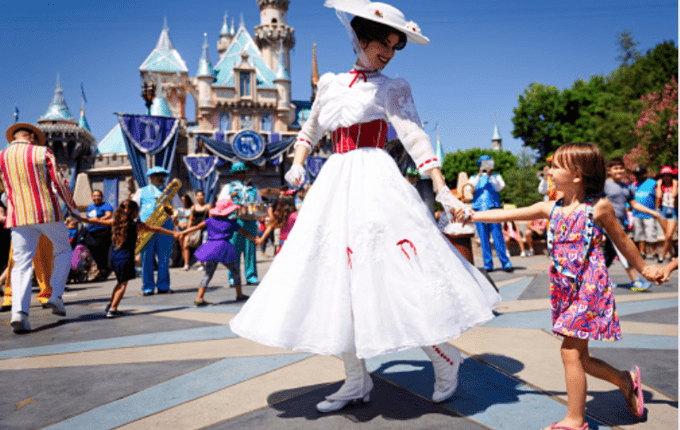 A Disney Character holding a little girls hand with a castle in the distance.