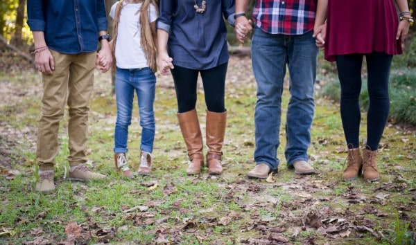 A group of people holding hands while standing in the grass.
