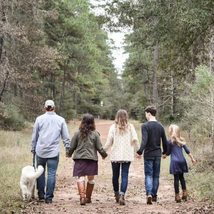 A group of people walking down a dirt road.