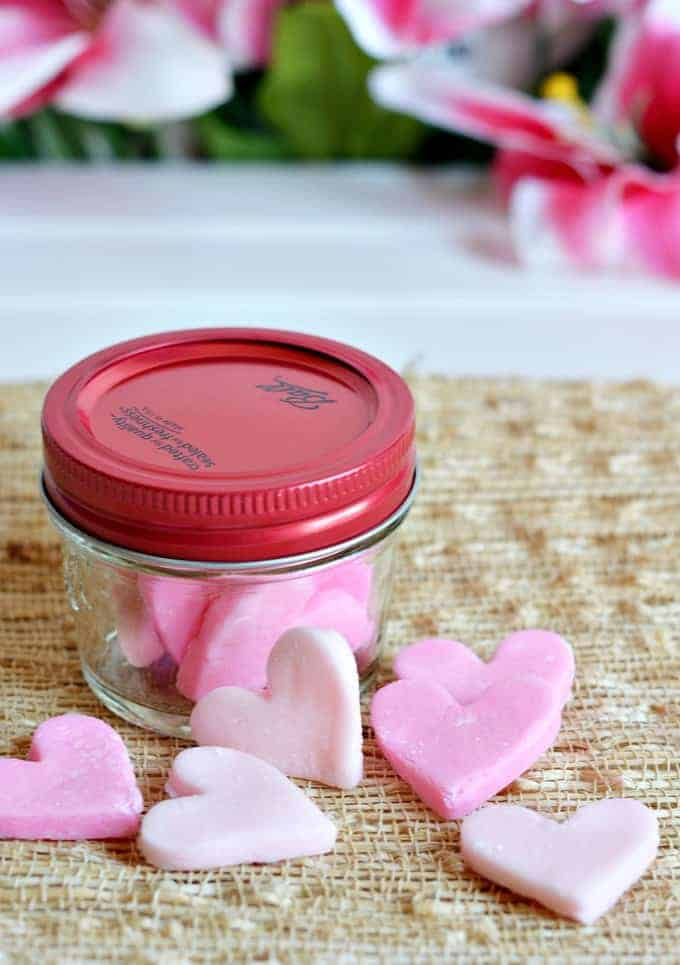 A small glass jar with a red lid and candy hearts around it.