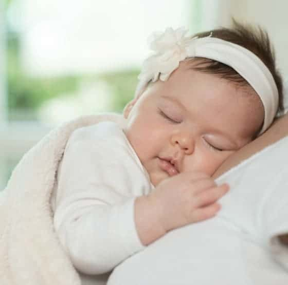 A woman holding a sleeping baby.