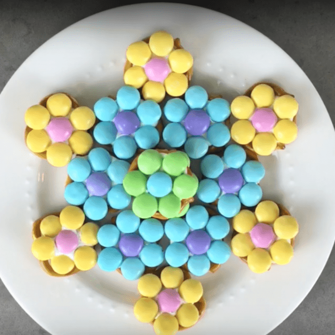 Colorful candies shaped into a flower sitting on a white plate.
