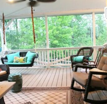 A screened in porch filled with porch furniture.
