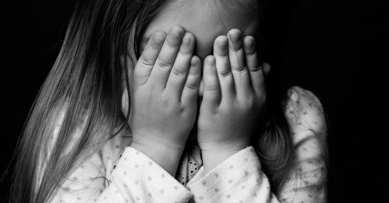 A little girl the her hands covering her eyes.