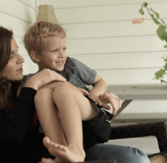 A woman sitting on a porch chair holding a little boy on her lap.