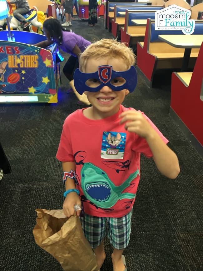A little boy wearing Chuck E Cheese plastic glasses and holding a brown paper bag.