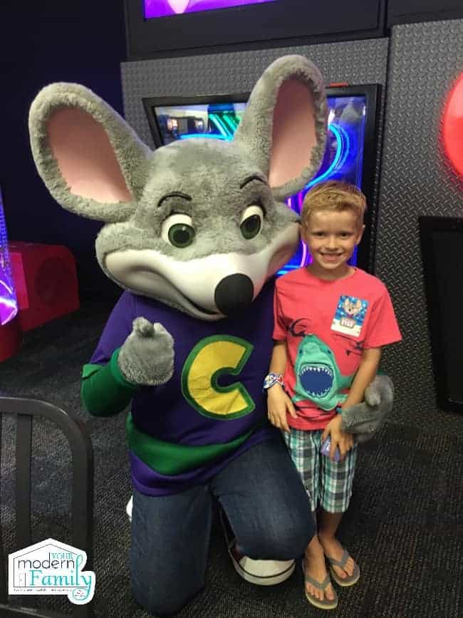 A little boy standing beside Chuck E Cheese posing for the camera.