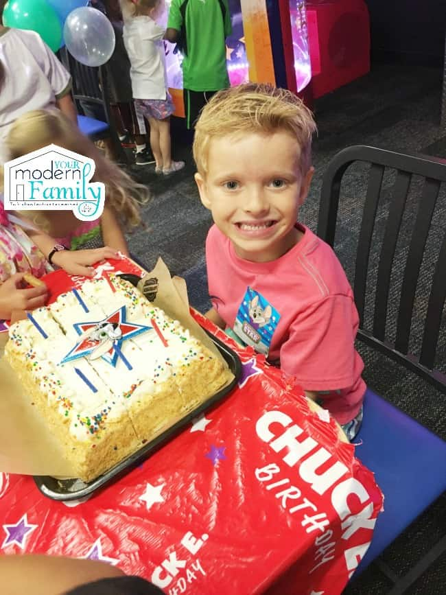 A little boy sitting at a table with a birthday cake.