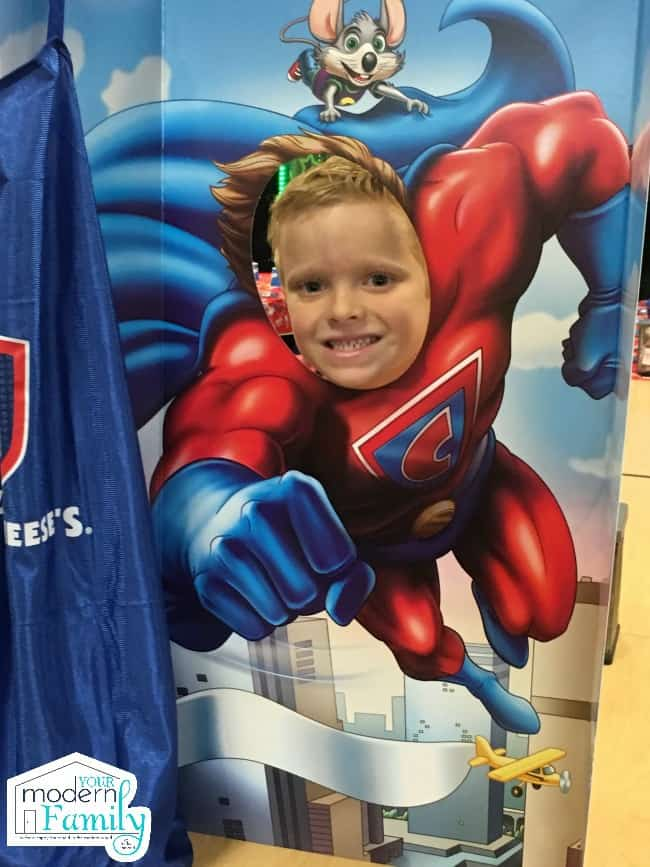 A little boy sticking his head through a hole of a photo poster of a super hero.