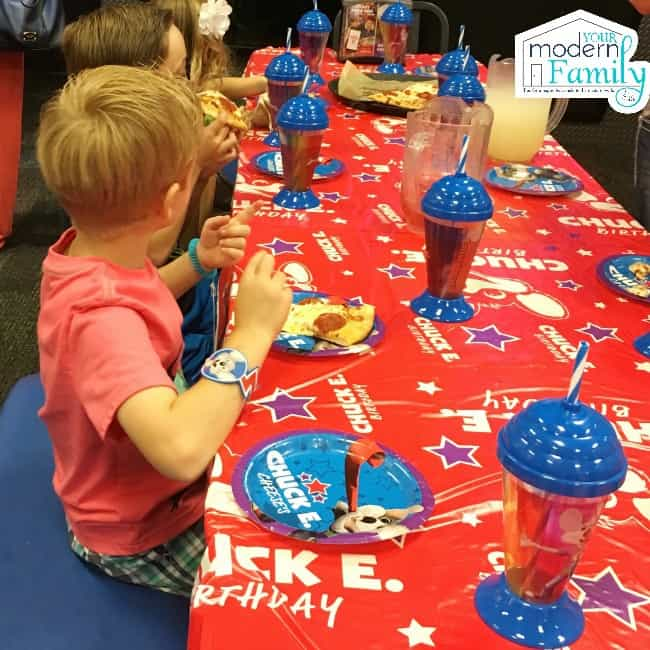 A little boy sitting at a table set for a birthday party.