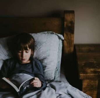 A young boy lying on a bed reading a book.