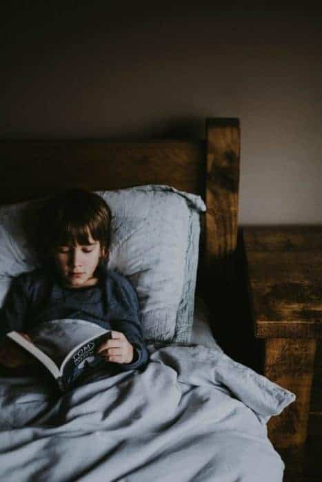 A boy lying in bed reading a book.