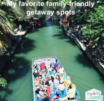A tour boat filled with people on a man made river with text above them.