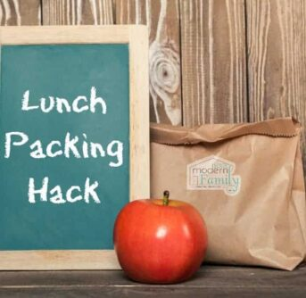 A small chalk board with text on it sitting beside an apple and a brown lunch bag.