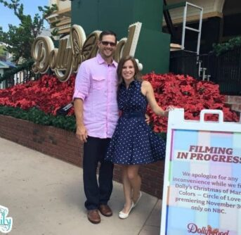 A couple standing in front of a sign in Dollywood.