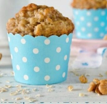 A blue and white polka dotted cup holding a banana muffin.
