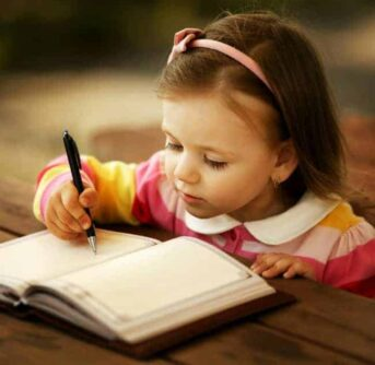 A little girl sitting at a table writing in a book.